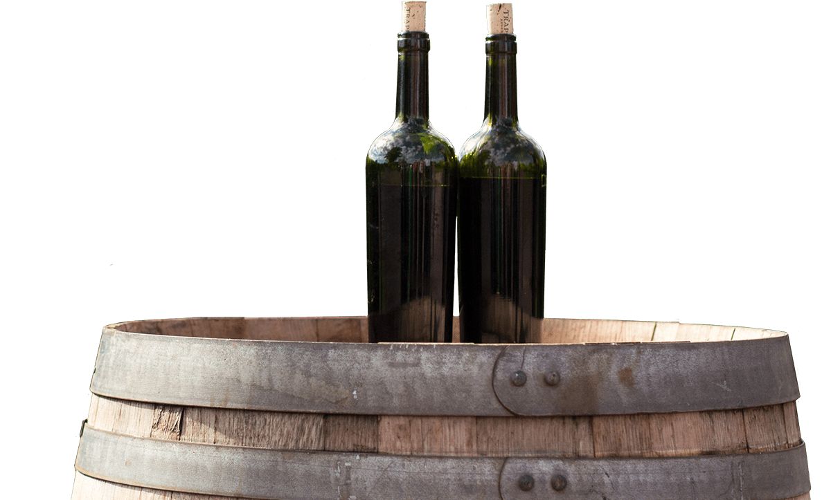 two green wine bottles sitting on barrell at Grapevine Distributors